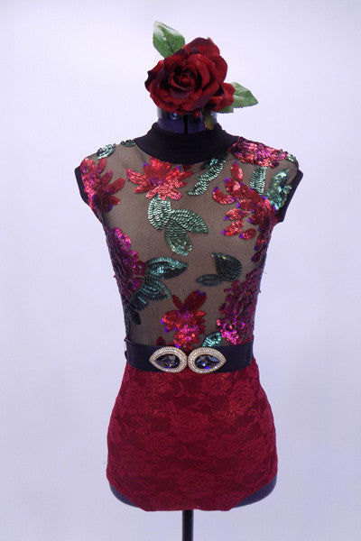 High collar leotard has nude front with black mesh adorned with large tropical sequin flowers of red, mauve and green. The open back is of sheer black mesh. The brief portion is a deep red lace and the costume is completed by a belt with large jeweled buckle accent and a floral hair accessory. Front