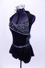 Black short unitard has peplum skirt & shawl collar. Bodice has mesh-chain design, silver cording & crystal accents. Has large beaded broach & hair accessory. Left side