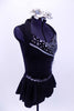Black short unitard has peplum skirt & shawl collar. Bodice has mesh-chain design, silver cording & crystal accents. Has large beaded broach & hair accessory. Right side