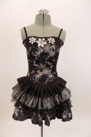 Black boned corset dress has grommet and ribbon lace back & silver floral lace overlay with jewel accents. The skirt is layers of pleated black & silver satin. Comes with hair accessory. Front