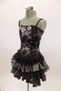 Black boned corset dress has grommet and ribbon lace back & silver floral lace overlay with jewel accents. The skirt is layers of pleated black & silver satin. Comes with hair accessory. Left side