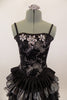 Black boned corset dress has grommet and ribbon lace back & silver floral lace overlay with jewel accents. The skirt is layers of pleated black & silver satin. Comes with hair accessory. Front zoomed