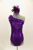 Purple metallic one-shoulder leotard has ruffle accent with crystals. Torso has sequined braiding & large jeweled applique. Comes with feathered hair accessory. Front