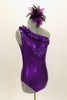 Purple metallic one-shoulder leotard has ruffle accent with crystals. Torso has sequined braiding & large jeweled applique. Comes with feathered hair accessory. Right side