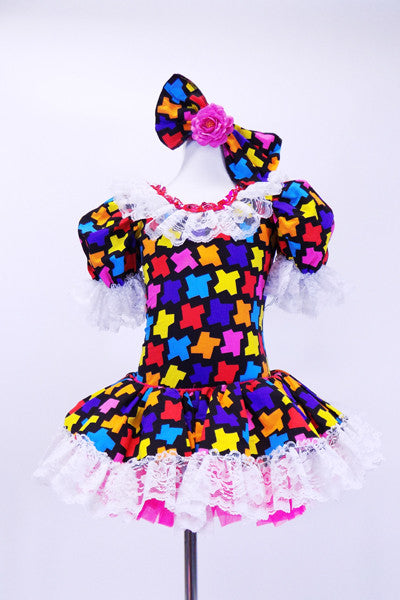 Black leotard dress has colorful puzzle piece decorative front with lace trim at neck sleeves and skirt. Dress has bright pink petticoat and matching bow hair accessory. Front