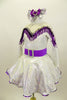 Silver dress has long sleeves and nude mesh upper. The bust-line is decorated with silver sequined, purple and white fringe. The dress has a wide purple belt with matching purple petticoat. Costume comes with silver and purple hair accessory. Left side