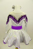Silver dress has long sleeves and nude mesh upper. The bust-line is decorated with silver sequined, purple and white fringe. The dress has a wide purple belt with matching purple petticoat. Costume comes with silver and purple hair accessory. Back