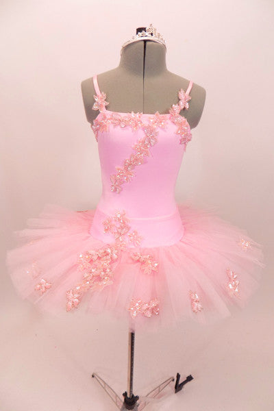 Pink platter tutu is hand tacked with zip-up bask & camisole leotard. Bodice, bask & tutu are adorned with beaded floral appliques. Comes with crystal tiara. Front