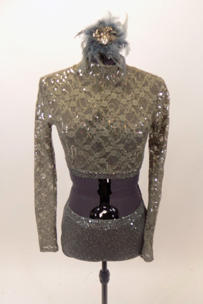 Taupe-grey lace sequined long-sleeved half top has high neck collar. Top is accompanied by matching glitter briefs and a feather and glitter hair accessory.  Front