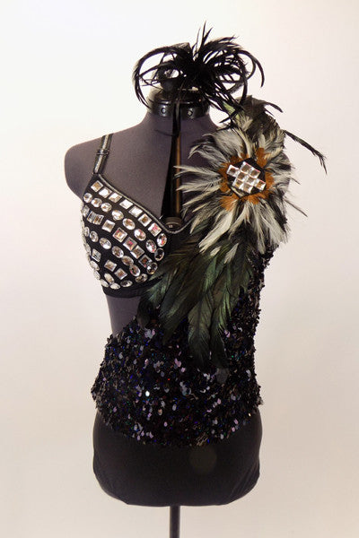 Black bra is covered with large jewel accents & sits beneath one shoulder, black sequined leotard dress with large feather accent on shoulder. Has feather hair accessory. Front.