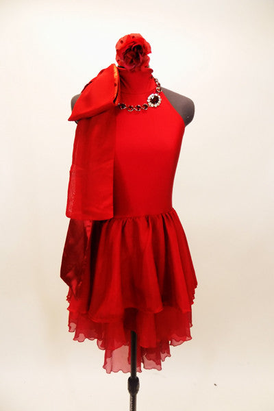 Red high neck, halter dress has attached skirt in layers of red chiffon. There is an attached red jeweled necklace and large satin bow that sits on right shoulder. Comes with red, crystaled hair accessory. Front