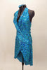 Bright aqua, fully sequined halter dress, has cross-over bodice as well as cross-over skirt with peek-a-boo front.  Comes with applique hair accessory.  Left side
