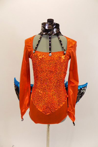 ong sleeved orange leotard that has square neckline and gold sequined front. There is a wide black sequined collar that attached to open neckline by three crystal covered straps. Sleeves have an attached padded blue fin with sequin accent. The black bustle is layers of sequin edged black tulle beneath a metallic blue ruffle. The finishing touch is a large black mesh fin that is attached securely to the center of the back. Front