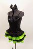 Black sequined & boned corset dress has grommet & lace  back. Has attached skirt with layers of ruffled green & black satin. Has separate panty & hair accessory. Left side