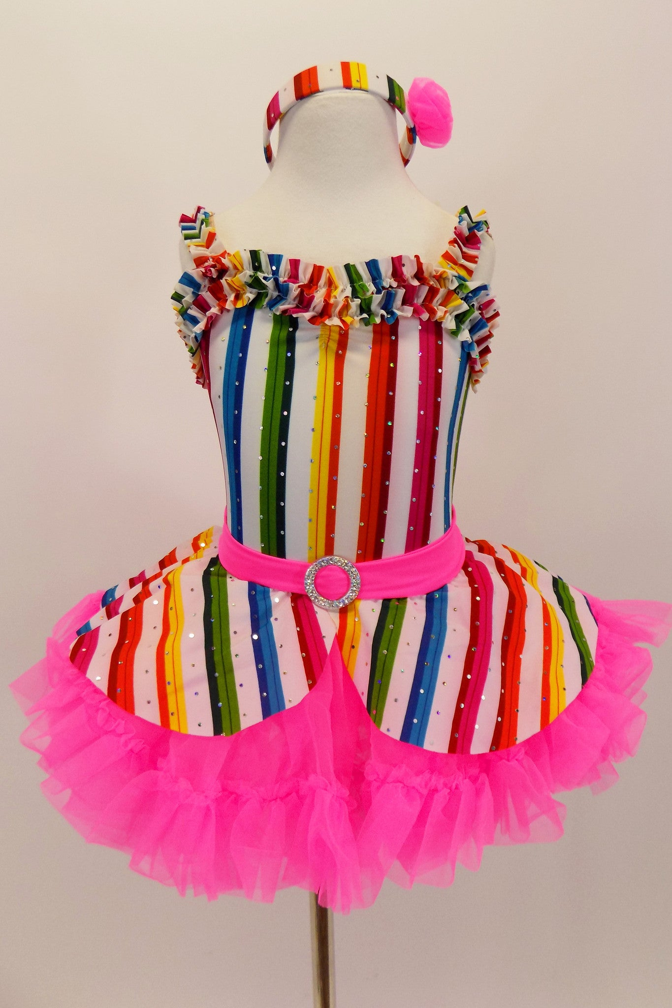White leotard dress has sequins,colorful  stripes &ruffled bodice.. Skirt sits over bright pink ruffled petticoat. Comes with white gloves, head-band & lollipop. Front