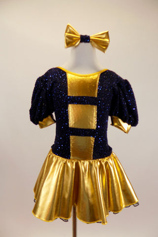 Navy blue crinkle lace dress has pouf sleeves with gold cuffs & gold striped inserts down front center of torso. Has attached gold skirt & matching hair bow. Front