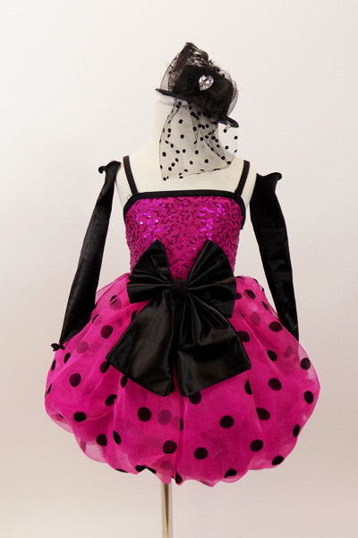 Hot pink sequined bodice has pink-black polk-a-dot bubble skirt with black satin front bow. Comes with black satin gauntlets and glittery black veiled top-hat. Front