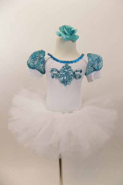 White velvet leotard has turquoise lace sleeves. Neckline has turquoise sequins & large jeweled applique. Comes with white tutu skirt & floral hair accessory. Front