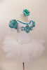 White velvet leotard has turquoise lace sleeves. Neckline has turquoise sequins & large jeweled applique. Comes with white tutu skirt & floral hair accessory. Right side