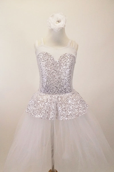 White and silver sequined romantic tutu dress has sweetheart neck-like peplum that sits on top of the long white soft tulle layers. The dress has double straps which cross at back. Comes with hair accessory. Front