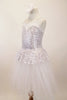 White and silver sequined romantic tutu dress has sweetheart neck-like peplum that sits on top of the long white soft tulle layers. The dress has double straps which cross at back. Comes with hair accessory. Left side