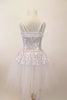 White and silver sequined romantic tutu dress has sweetheart neck-like peplum that sits on top of the long white soft tulle layers. The dress has double straps which cross at back. Comes with hair accessory. Back