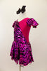 Hot pink metallic and zebra pattern, cross front leotard dress has zebra print ruffled cap sleeves and skirt with solid pink back.  Comes with black bow hair accessory. Left side
