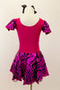 Hot pink metallic and zebra pattern, cross front leotard dress has zebra print ruffled cap sleeves and skirt with solid pink back. Comes with black bow hair accessory. Back