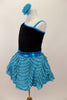 Black velvet leotard has single sleeve of soft, layered turquoise ruffles. Comes with matching turquoise ruffled skirt with petticoat and floral hair accessory. Left side