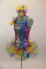 Rainbow colored square-sequined camisole leotard has attached rainbow colored, curly organza ruffle skirt. Comes with matching rainbow hair accessory.  Feft side