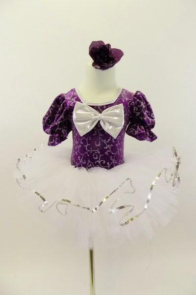 Purple velvet leotard has pouf sleeves & silver pattern. Neck-line is square cut with silver edging & large silver front bow. Comes with white pull-on tutu & floral hair accessory. Front