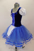 Peasant style  ballet dress has blue velvet bodice ,corset tie front & pouf sleeves. Skirt is layers of blue tulle with ribbon accent and a white apron. Comes with hair accessory. Left Side