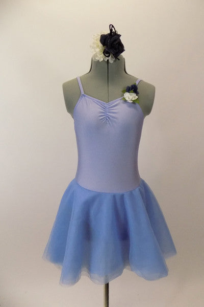 Pale blue leotard dress with floral accent has low back with looping cross strap design at lower back. The attached skirt is sheer layers of pale blue. Comes with hair accessory. Front