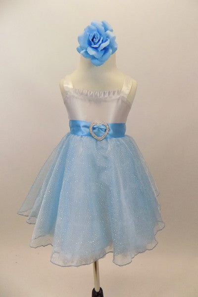 White satin bodice dress has front ruffle. Sparking blue organza rests over blue tulle. Wide blue satin waist sash has crystal heart accent. Has rose hair clip. Front
