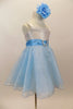 White satin bodice dress has front ruffle. Sparking blue organza rests over blue tulle. Wide blue satin waist sash has crystal heart accent. Has rose hair clip. Right side