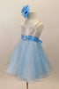 White satin bodice dress has front ruffle. Sparking blue organza rests over blue tulle. Wide blue satin waist sash has crystal heart accent. Has rose hair clip. Left side