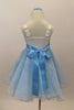 White satin bodice dress has front ruffle. Sparking blue organza rests over blue tulle. Wide blue satin waist sash has crystal heart accent. Has rose hair clip. Back