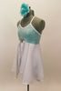Aqua sequined leotard dress has cross back straps. Attached open-front white chiffon skirt has crystal rose brooch accent. Comes with aqua floral hair piece. Left side