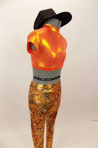 Bright orange metallic high neck half top has keyhole back. Accompanied by metallic orange leggings with a black & silver splatter pattern & black baseball cap. Left side