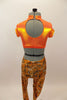 Bright orange metallic high neck half top has keyhole back. Accompanied by metallic orange leggings with a black & silver splatter pattern & black baseball cap. Back