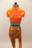Bright orange metallic high neck half top has keyhole back. Accompanied by metallic orange leggings with a black & silver splatter pattern & black baseball cap. Front
