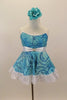 Camisole leotard dress has swirls of blues on aqua base. Has a white petticoat and wide lace trim. White satin waist sash had a crystal heart. Has floral hair accessory. Front