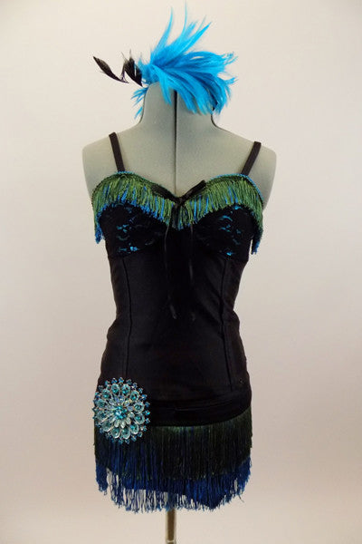 Roaring 20s style costume has bodice with lace bra & green-turquoise fringe. Black briefs have the matching fringe and a huge round crystal brooch at hip. Has turquoise feather hair piece. Front