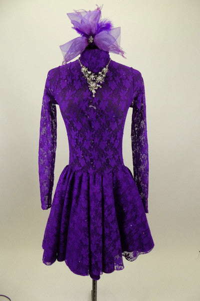 Purple lace high neck, long sleeved open back dress has large jeweled crystal attached necklace. Comes with large matching purple hair accessory. Front