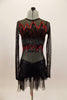 Black long sleeved sheer leotard has front bust panel in flame pattern edged in red sequins. Black shorts have flame pattern repeated on back with sheer bustle. Front