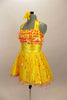 Orange & yellow paillettes, feathers & crystals adorn yellow satin dress with halter neck, skirt with yellow base on orange petticoat & matching hair accessory. Left side