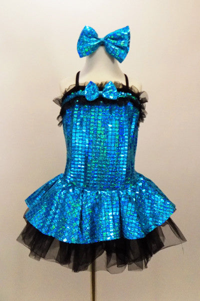 Turquoise holographic square sequined dress has bow tie accent & ruffle. Skirt has layers of black tricot petticoat beneath. Comes with matching shoe & bows. Front