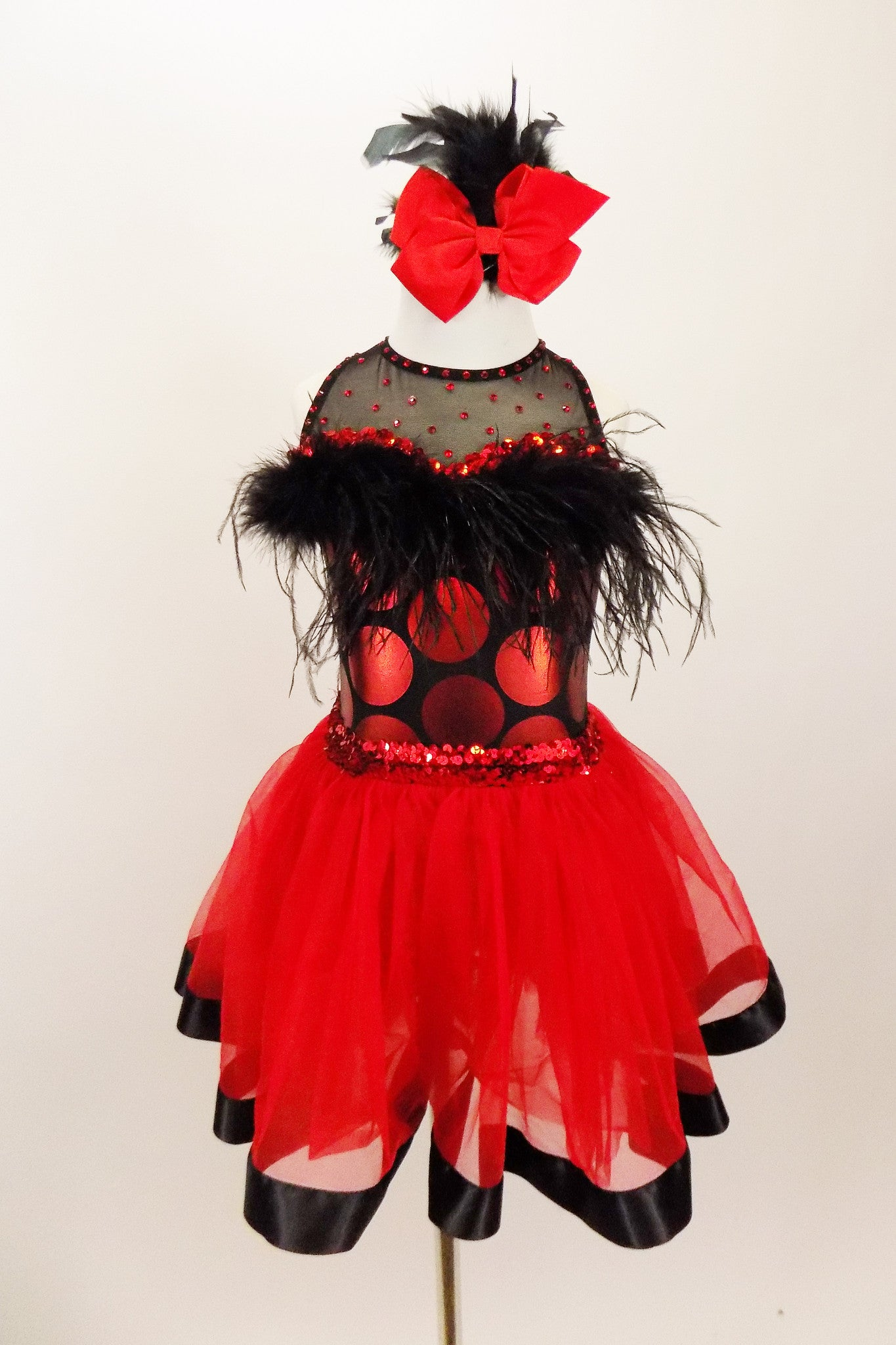 Dress has bodice with sweetheart neck polka dots & black mesh covered with crystals & feather trim. Skirt is red tricot with black satin hem. Has hair accessory. Front