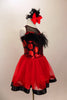 Dress has bodice with sweetheart neck polka dots & black mesh covered with crystals & feather trim. Skirt is red tricot with black satin hem. Has hair accessory. Right side