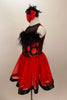 Dress has bodice with sweetheart neck polka dots & black mesh covered with crystals & feather trim. Skirt is red tricot with black satin hem. Has hair accessory. Left side